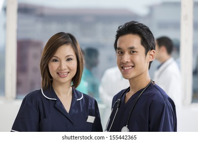 Two Asian Nurse's standing in a hospital with there team in background.