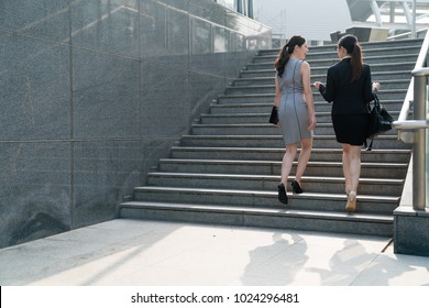 Two Asian office lady walk up the stairs and discuss with each other. On a back view. They both wearing high heels and formal suits dress carrying bags. Talking about the business stuff and costumers.