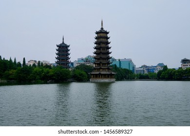 two asian pagodas (Sun Moon Pagoda) above peaceful lake. Reflection in water. Forest trees and city skyline as background. In Guilin city Guangxi China.