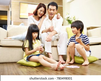 two asian parents watching children playing cards on floor.