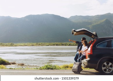 Two Asian people sitting on car truck,they're looking at the Mountain View and take a picture.