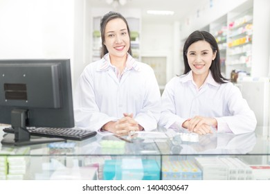 two asian pharmacist standing in drugstore, the feeling happy and smile, teamwork and professional worker