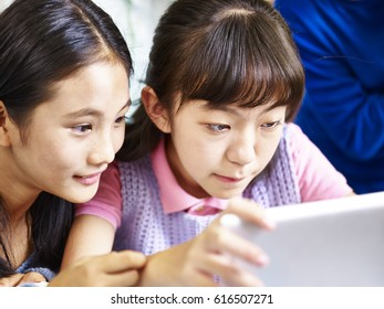 two asian primary school students using digital tablet together