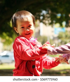 two asian smiling girls hand in hand playing and holding in a park