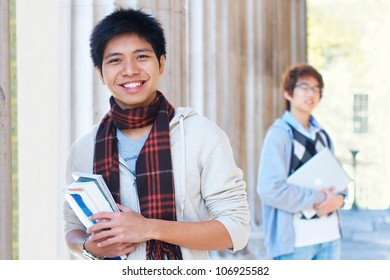 Two asian students holding books outdoors