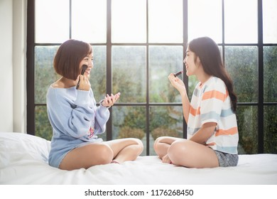 Two Asian teenage girls having fun while applying make up on the bed in the morning