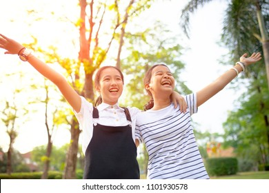 two asian teenager laughing with happiness emotion in green natural park