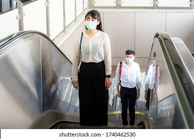 Two Asian wearing face mask and keep distance 6 feet to other people protect from COVID-19 viruses for social distancing for infection risk at escalator in subway station in Bangkok, Thailand.