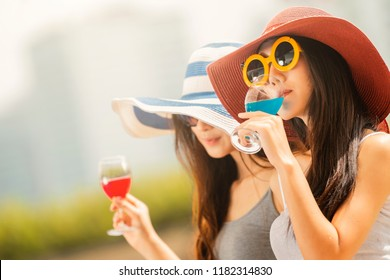 Two asian woman long haired girl in hat , eyeglasses with nude makeup sitting with cocktail at outdoor party.