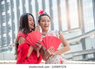 Two Asian woman in traditional chinese long dress, cheongsam, black hair, carrying Red envelope or gift voucher for reward as a customer for Chinese New Year festival, celebration time.