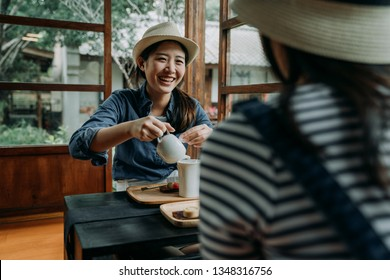 two asian woman travelers in hats in kyoto japan. girl smiling pouring tea into ceramic cup bowl on table. happy friends travel relax enjoy japanese culture chado in wooden house with spring garden