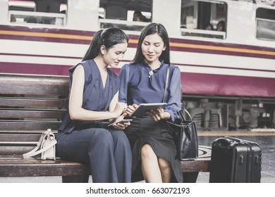 Two asian woman using tablet at outdoor place with attractive smiling, woman resting concept.