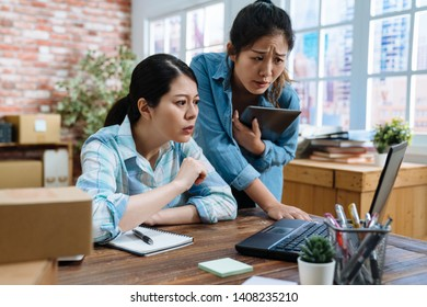two asian woman worker working in postal parcel delivery service office. frowning confused coworkers discussing laptop and solve problem of annoyed customer online on internet store