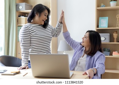 Two Asian woman working in the house.