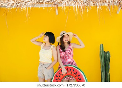 Two asian women bestfriend closefriend on summer vacation. Traveling together on the beach. Over yellow background.