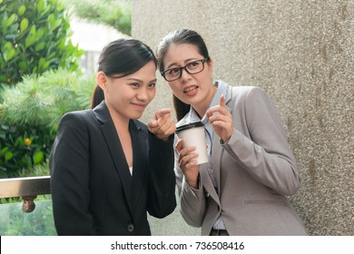 two Asian women enjoy workplace bullying conversation about another colleague rumor gossip and pointing outdoor of the company.