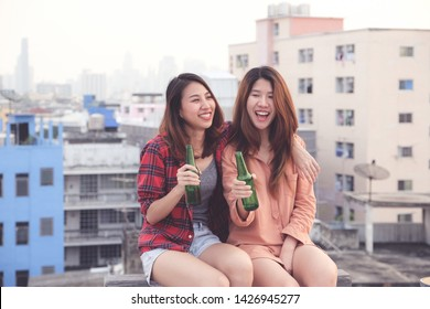 Two asian women friends drinking at rooftop party, outdoors celebration, friendship, LGBT couple