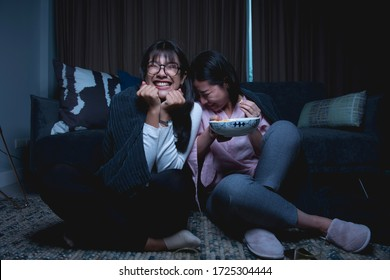 two asian women with a popcorn watch a horror film in livingroom