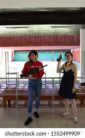 Two of asian women posing with the gun and playing armer gun sport field