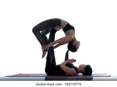 Two asian women practicing yoga on a white background