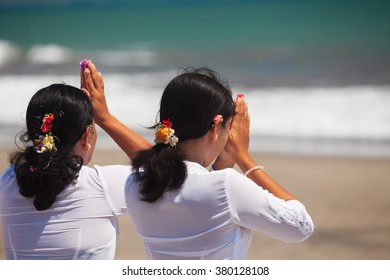 Two asian women with praying hands on ocean beach at ceremony Melasti before Balinese New Year and silence day Nyepi. Holidays, festivals, rituals, art, culture of Indonesian people and Bali island.