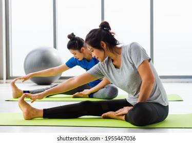 Zwei asiatische Frauen sportliche attraktive Menschen, die gemeinsam Yoga-Unterricht üben, trainieren im Fitness-GYM, junge und ältere Frauen trainieren Yoga in Yoga-Kursen, Sport gesund Lifestyle-Lifestyle