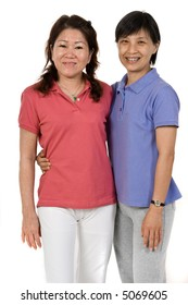 Two Asian women standing together in studio on white background
