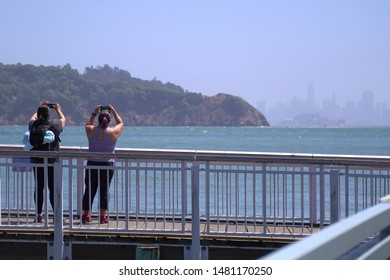 Two asian women taking a scenic shot of San Francisco with their smart phones from Tiburon. Angel Island can also be seen.