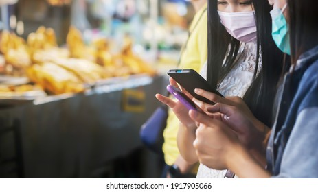 Two Asian women wearing face mask holding smartphones choose and looking for things to buy in a street food market. Asian street food market during the Coronavirus outbreak. Focus on smartphone.