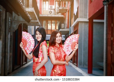 Two Asian women wearing a red traditional Chinese dress. New Year and Chinese New Year Festival