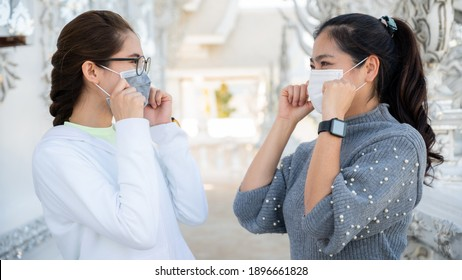 Two Asian women wearing surgical mask while meeting in covid-19 pandemic outbreak. New normal lifestyle, should wear a mask to keep your nose and mouth covered when in public. - Shutterstock ID 1896661828