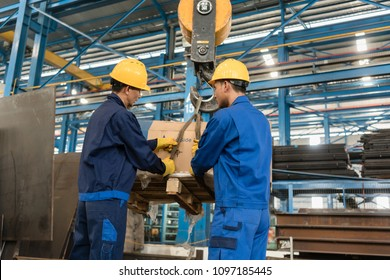Two Asian workers handling heavy loading lifted by crane in the interior of a metallurgical factory