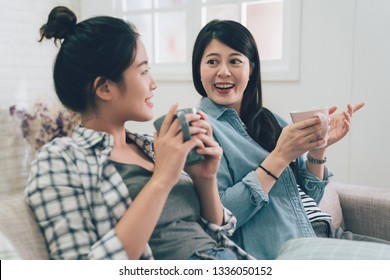 two asian young girls roommates relaxing on sofa at home drinking hot tea looking outside enjoy the city view from window on sunny day. women stay indoors lazy chatting talking on couch on weekends.