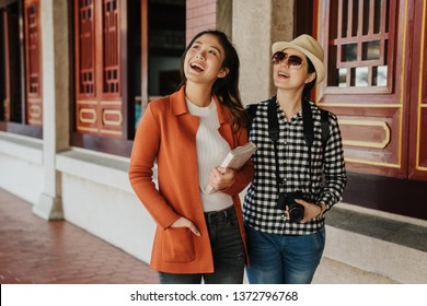 two asian young girls tourists visiting temple of heaven in beijing china walking in peaceful hallway through the window. women travelers standing in corridor look up ceiling holding book and camera.