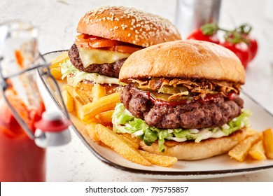 Two assorted burgers on crusty toasted buns with all the trimmings served with French fries and ketchup on a rectangular platter