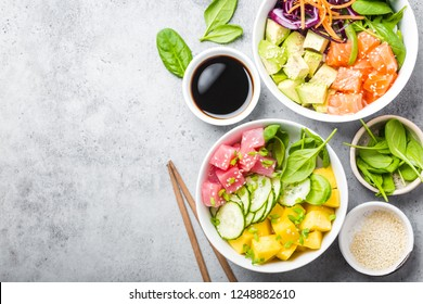 Two assorted poke bowls with raw fish and vegetables, space for text. Top view, close up. Hawaiian dish, rustic stone background. Healthy clean eating concept. Poke with raw fish slices, copy space