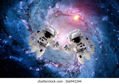Two astronaut spaceman outer space teamwork hands man people. Elements of this image furnished by NASA.