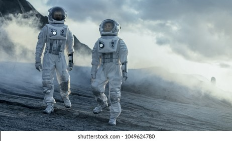 Two Astronauts Explore Rocky Alien Planet in the Day Time. Near Future and Technological Advance Brings Space Exploration, Travel, Colonization Concept.