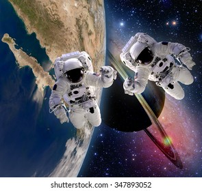 Two astronauts handshake spaceman sun saturn planet sci fi earth outer space galaxy. Elements of this image furnished by NASA.