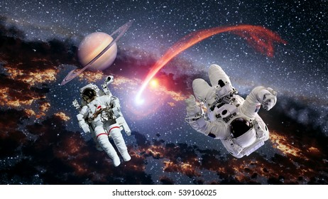 Two astronauts planet Saturn spaceman comet space suit galaxy universe. Elements of this image furnished by NASA.