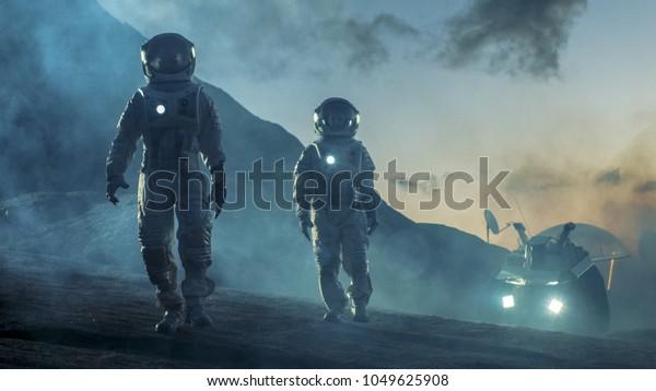 Два космонавта в космическом костюме уверенно ходят по чужой планете, исследование поверхности планеты. В фоновом исследовательском базе/станции и ровера. Космические путешествия, концепция колонизации.
