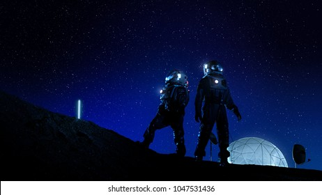 Two Astronauts in Space Suits Stand on the Moon Looking at the Beautiful Nght Sky Full of Stars. In the Background Lunar Base with Geodesic Dome. Moon Colonization and Space Travel Concept.
