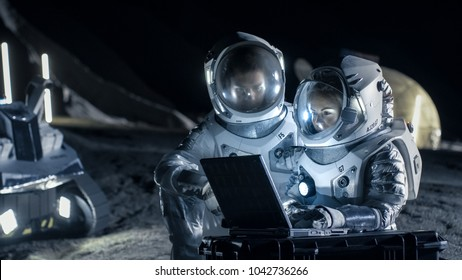 Two Astronauts Wearing Space Suits Work on a Laptop, Exploring Newly Discovered Planet, Send Communicating Signal to Earth. Space Travel, Interstellar Exploration and Colonization Concept.