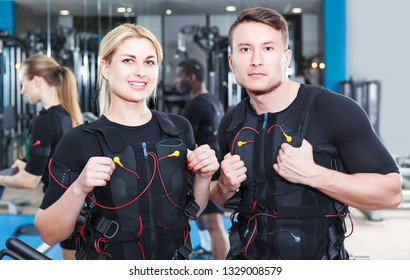 two athletes   dressed in EMS vests in modern busy gym