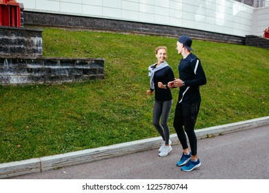 two athletes have met in the street. side view full length shot. copy space