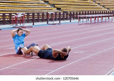 Two athletes help each other to pump the abdominal at the stadium on a sunny day