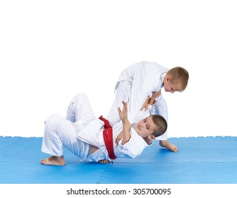 Two athletes in judogi are training throws