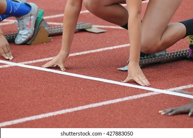 Two athletes line up on track and prepare to race