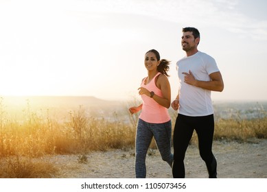Two athletes running at sunset. Man and woman training together.