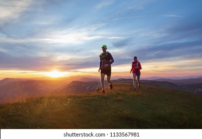 Two athletes trail running in the hills during sunset. Shallow D.O.F. and with motion blur.